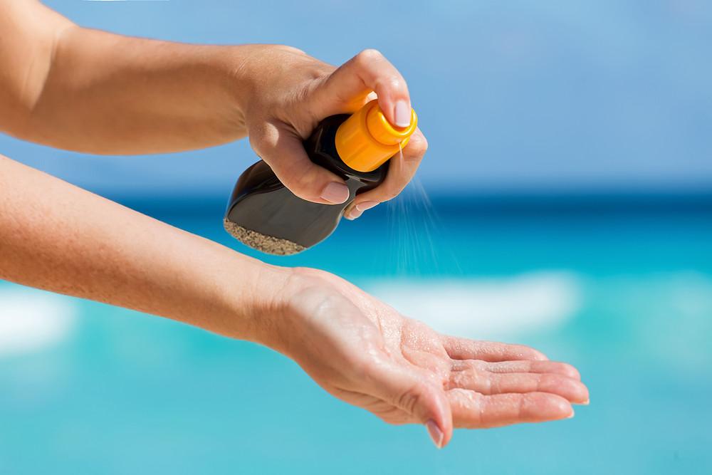 Sunscreen spray being applied on hand. beach