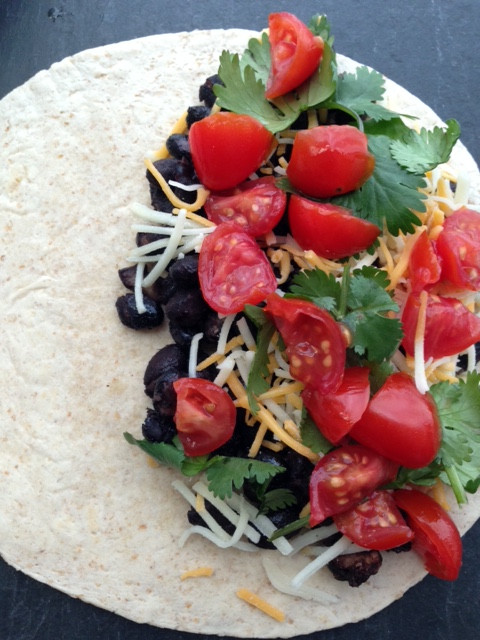 A black bean quesadilla with black beans, tomatoes, cilantro and cheese on tortilla