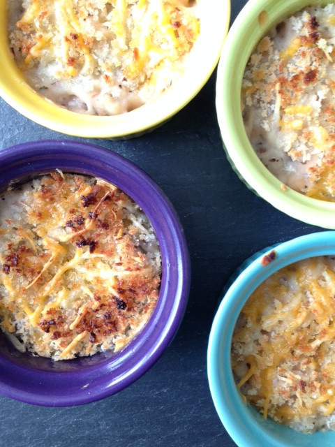 White bean dip with bread crumb and cheese topping in blue and purple dishes