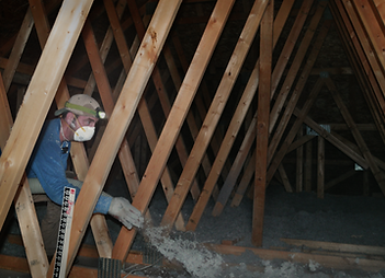 Insulation installer in attic blowing cellulose insulation