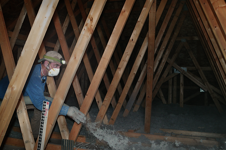Insulation installer in attic blowing cellulose