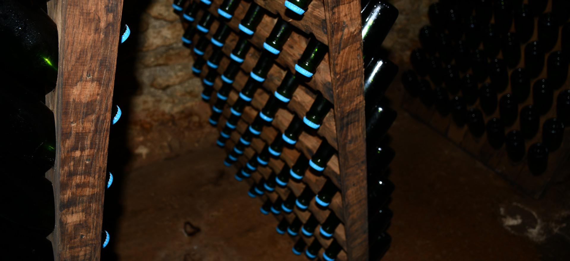 Hier befinden sich die Chamapgner in der Remuage. Es bezwecht das die Hefe Rückstände langsam in den Flaschenhals kommen um diese vom Saft zu trennen und somit auch die Gärung abzuschliessen. Hier sehen wir das dies täglich von Hand gemacht wird. Dabei werden alle Flaschen täglich leicht gedreht.
