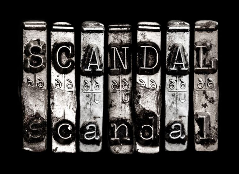 "Image of pieces of old lead printing press type spelling out the word ""scandal"""