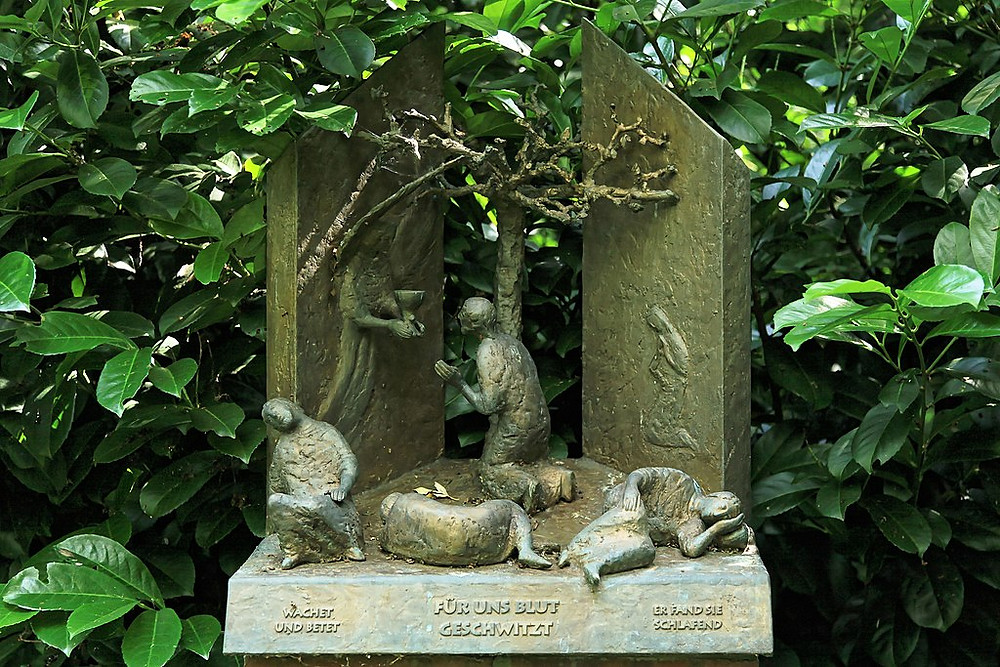 Modern sculpture of figures in a garden setting with several people asleep and an upright figure receiving a chalice from a winged character.