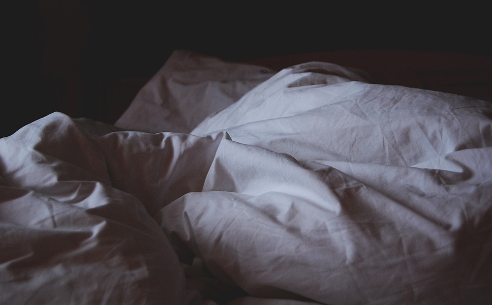Dark image of rumpled white sheets and two wrinkled pillows.