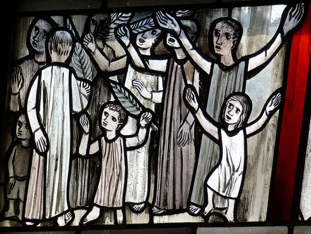 Segment of a stained glass window with people waving palm fronds.