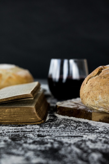 Photo of rustic loaf of bread, glass of wine, and an old book which looks like a Bible