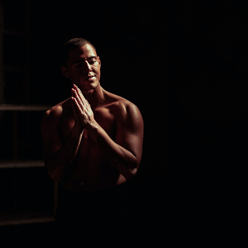 Male person of color in a dark room with palms pressed together in the namaste motion.