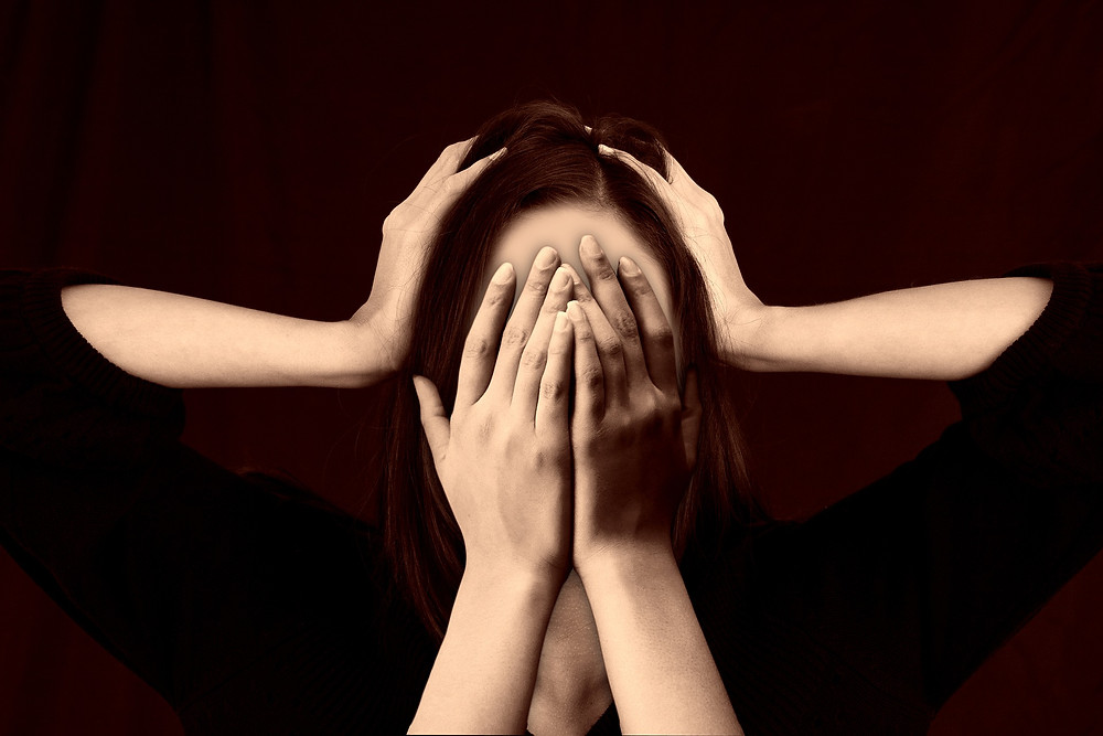 Picture of a woman covering her face with her hands, while two arms reach in to press against her head. Implies shame and pressure.