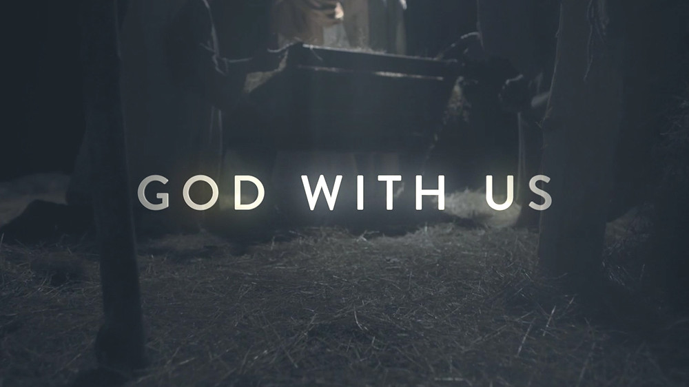 "Dark, indistinct image with glowing words reading ""God with us."""