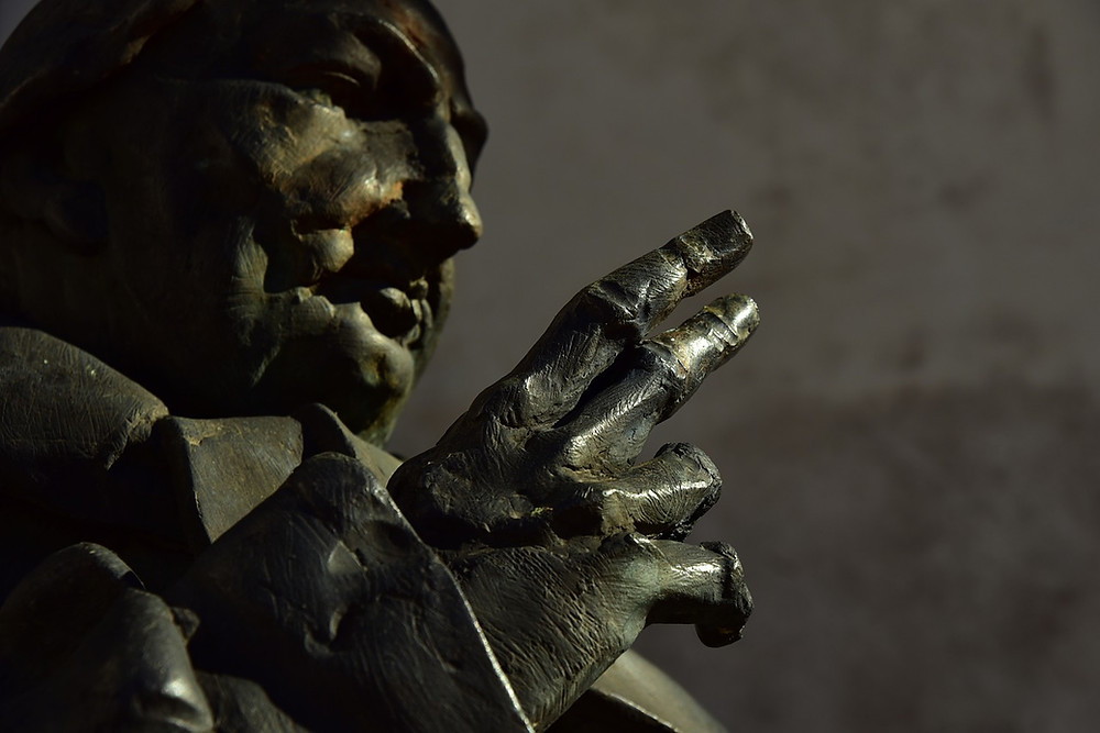 Close up of bronze statue of a priest's face and hand.