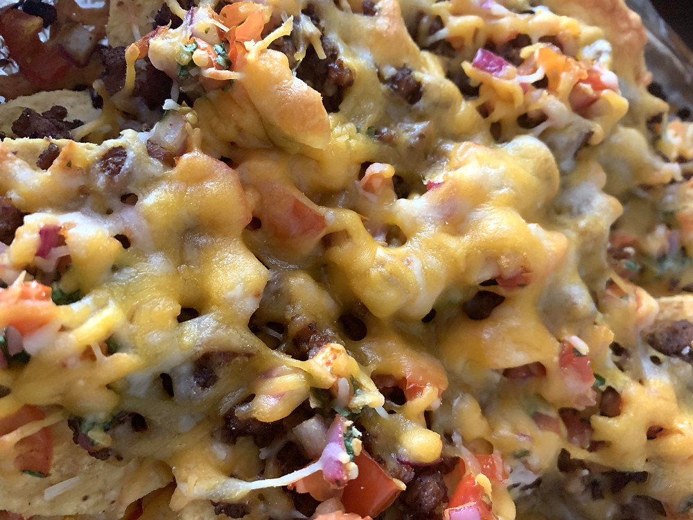 Vegetarian Nachos loaded with vegan meat, onion, salsa, and cheese