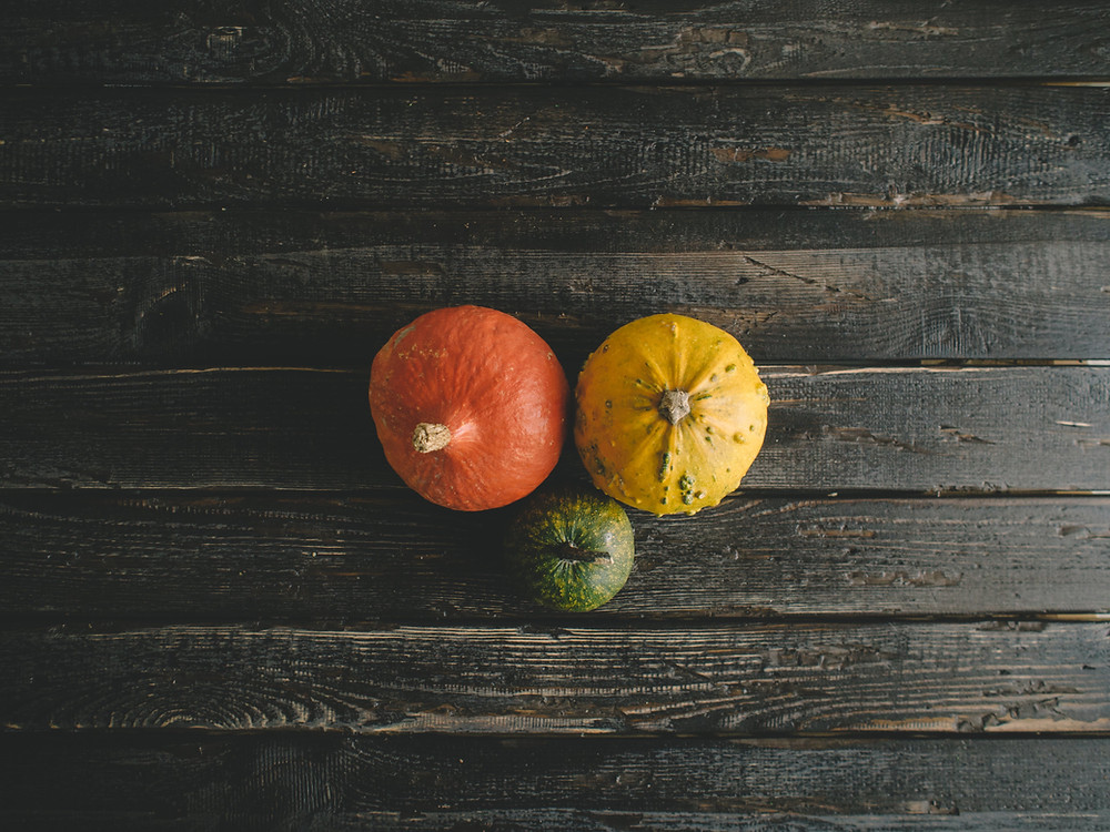 3 red, yellow, and green pumpkins on wooden surface