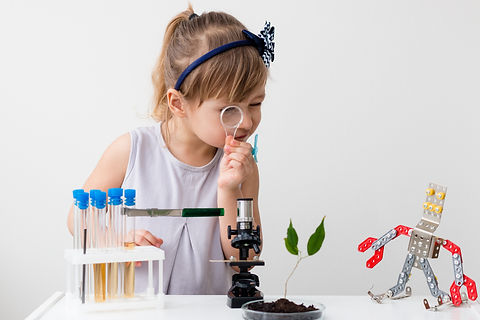 Little girl is behind the desk. Microsco