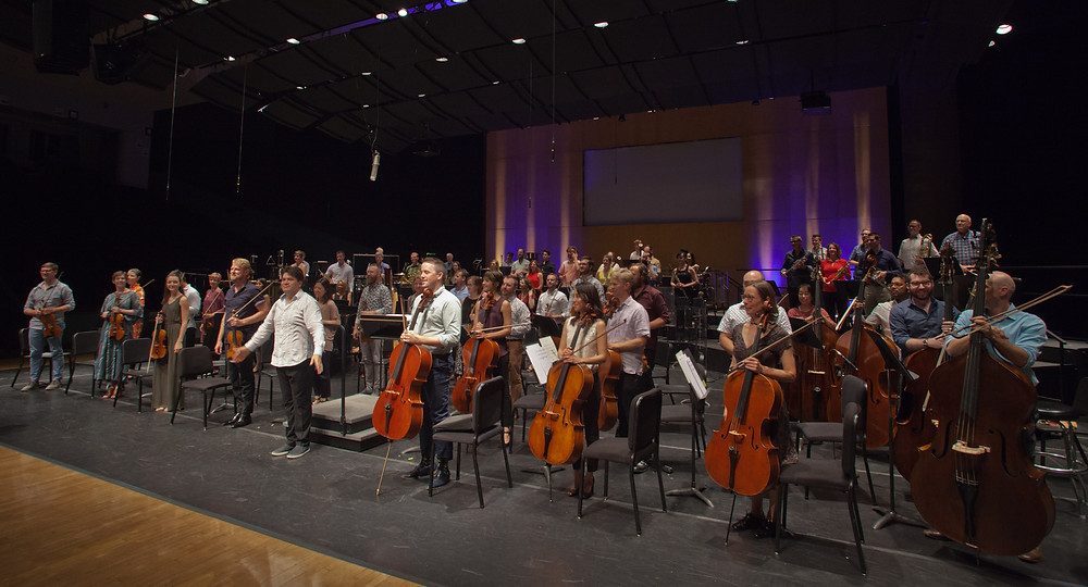 """Orchestra and conductor take bows at performance"""