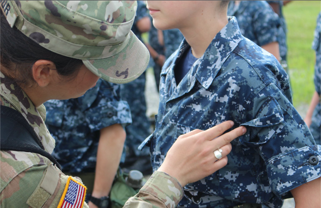 A volunteer conducts a uniform inspection.