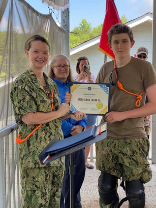 A volunteer presents a certificate to a cadet at summer training.