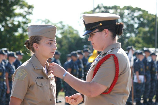 An active duty Navy volunteer pins chief anchors onto a new