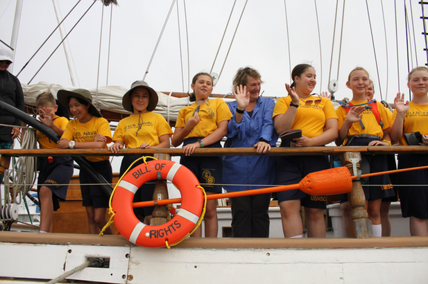 A volunteer poses with cadets during a sailing training.