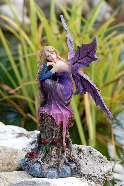 Fée Violette assise sur un tronc