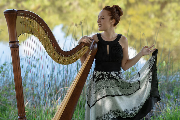 Harpist Natalie Wagner with her pedal harp performing outdoors