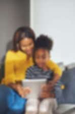 Little black girl and mom with tablet si