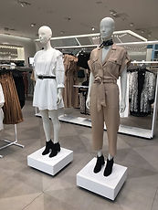 Mannequins dressed in white and beige.