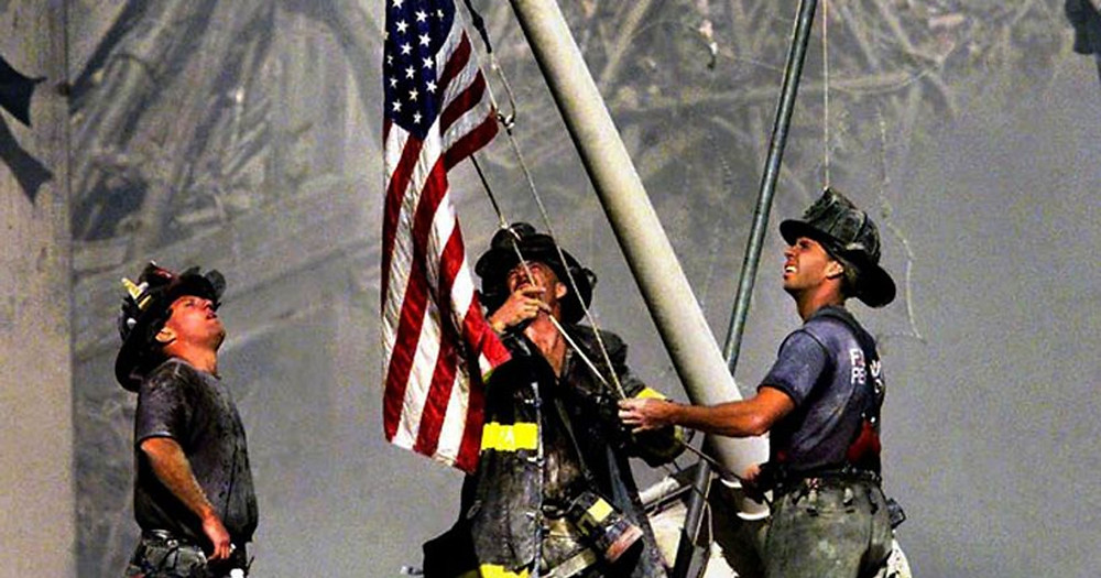 Firemen at ground zero raise a flag they got from a boat at the nearby docks.