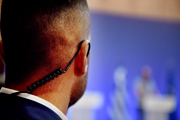 A Security Guard wears an ear headset du