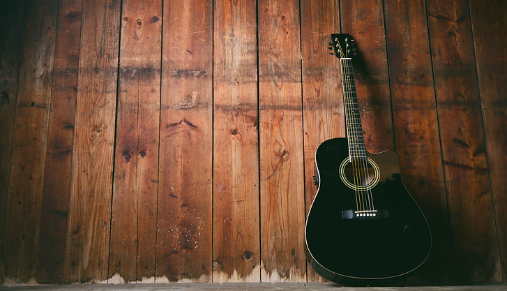 Acoustic guitar on a wooden texture with