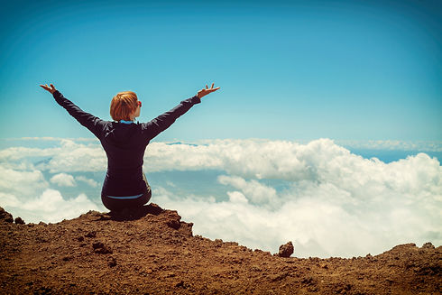 person-sitting-on-cliff-raising-up-both-