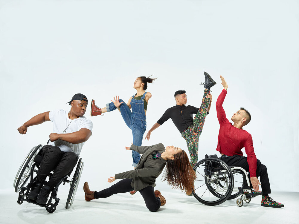 Five Axis Dance Company dancers pose in a room with white floor, white background. Dancers are either in a wheelchair, standing or on the floor with a bent knee as they hold their pose.