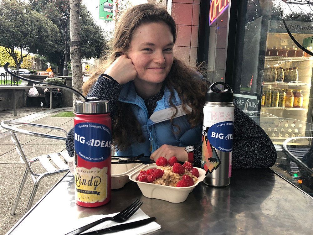 Tess smiles at the camera. She has white skin, has her long dark blonde hair fall on her shoulders. In front of Tess is a paper box with a cinnamon bun with raspberries on top. There are two water bottles with Big Ideas stickers on either side of the cinnamon bun.  In the background is the pavement, trees and the inside of Cinnaholic Bakery can be seen.