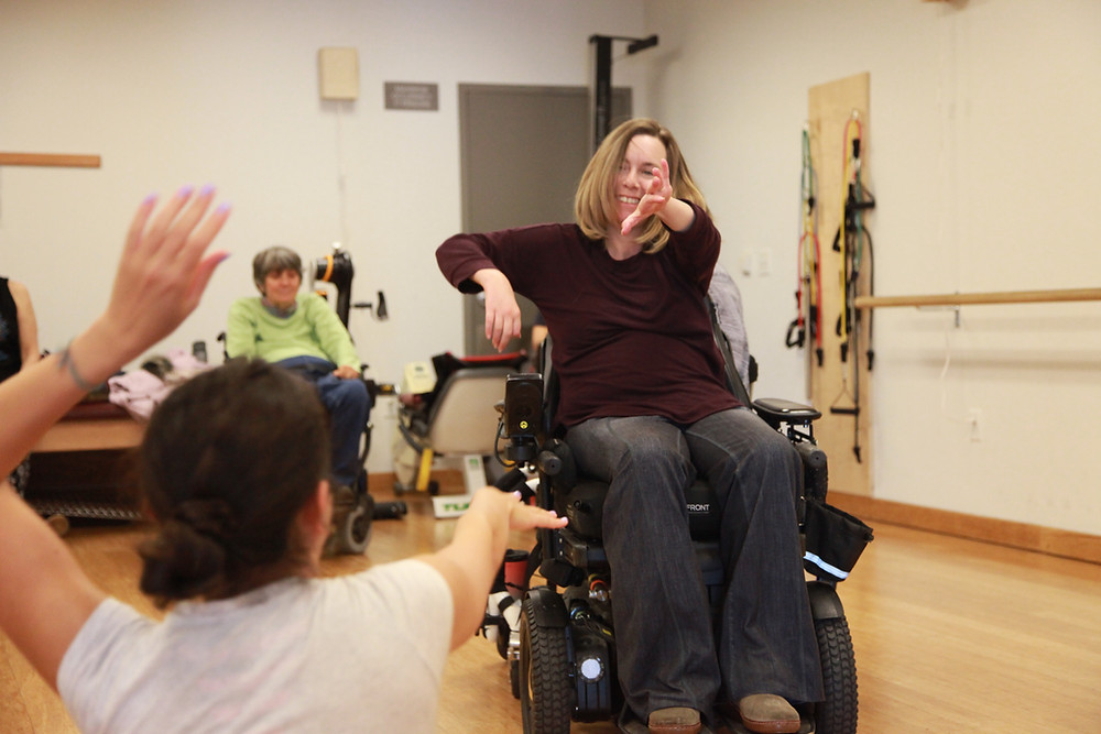 Yagmur and a dance class participant reach for one another. Yagmur is in seated position on the floor, and the participant, a women with white skin, short blonde hair is seated in a wheelchair, reaching with her arms towards Yagmur. She smiles at Yagmur, who has her back turned to us.