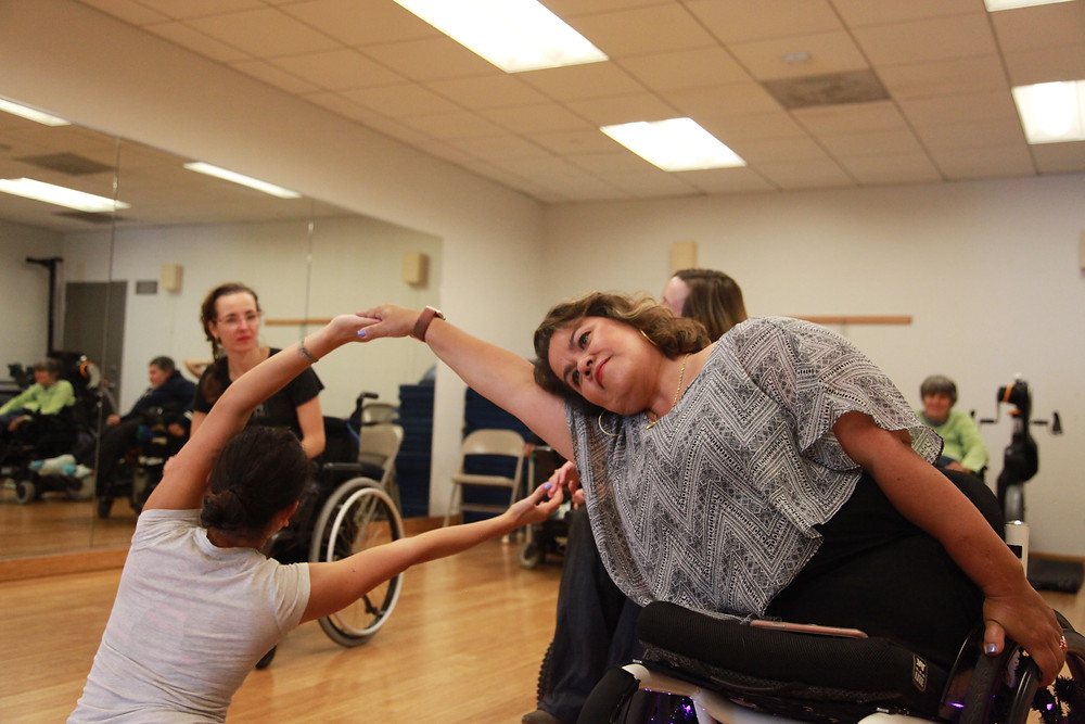 The photo includes a dancer holding her wheelchair with her left hand hand and reaching out with her right arm to hold hands with an individual with her back turned to us. She reaches her right arm to hold hands with another individual in a wheelchair, located behind the other wheelchair user. Another individual in the background gazes at the dancers holding the pose. The photo is taken in a dance studio with a wide mirror on the wall and with bright lighting.