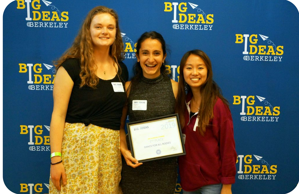 Tess, Yagmur and Michelle (left to right) posing while Yagmur holds a framed certificate for their award as 2nd place winners in the Arts & Social Change Category in Big Ideas.