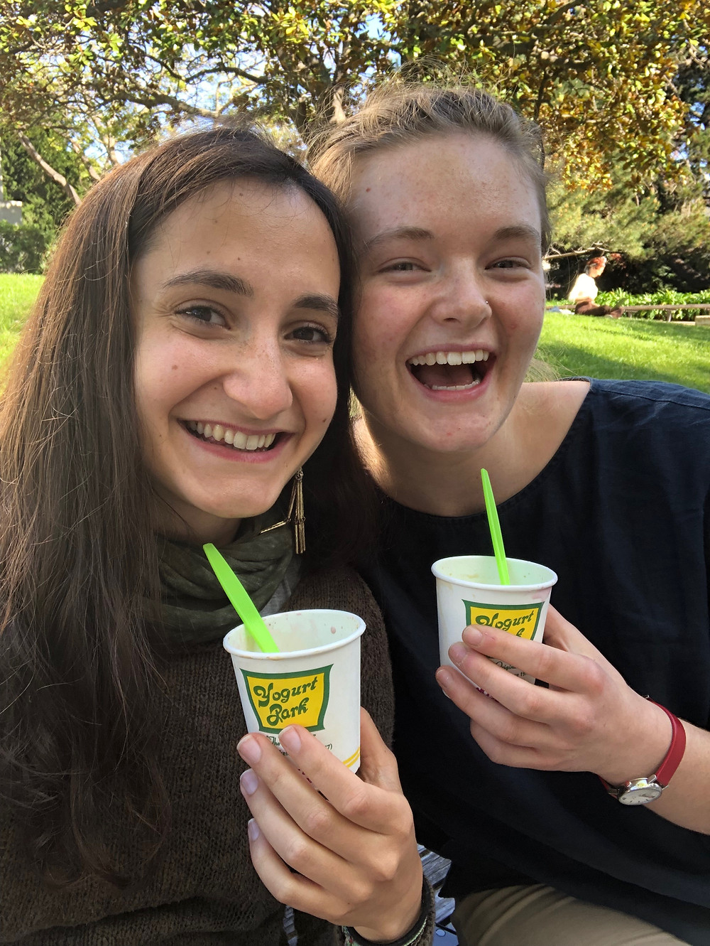 Yagmur and Tess smile at the camera, holding white paper cups that have Yogurt Park written on them in green and there is a florescent green plastic spoon in them. Yagmur has long brown hair, she is fair skinned, wears a dark green scarf and dark green top. Tess has a big smile on her face, has white skin and her hair in a bun. She wears a dark blue top. In the background is a grassy area and a big tree with many branches and green leaves.