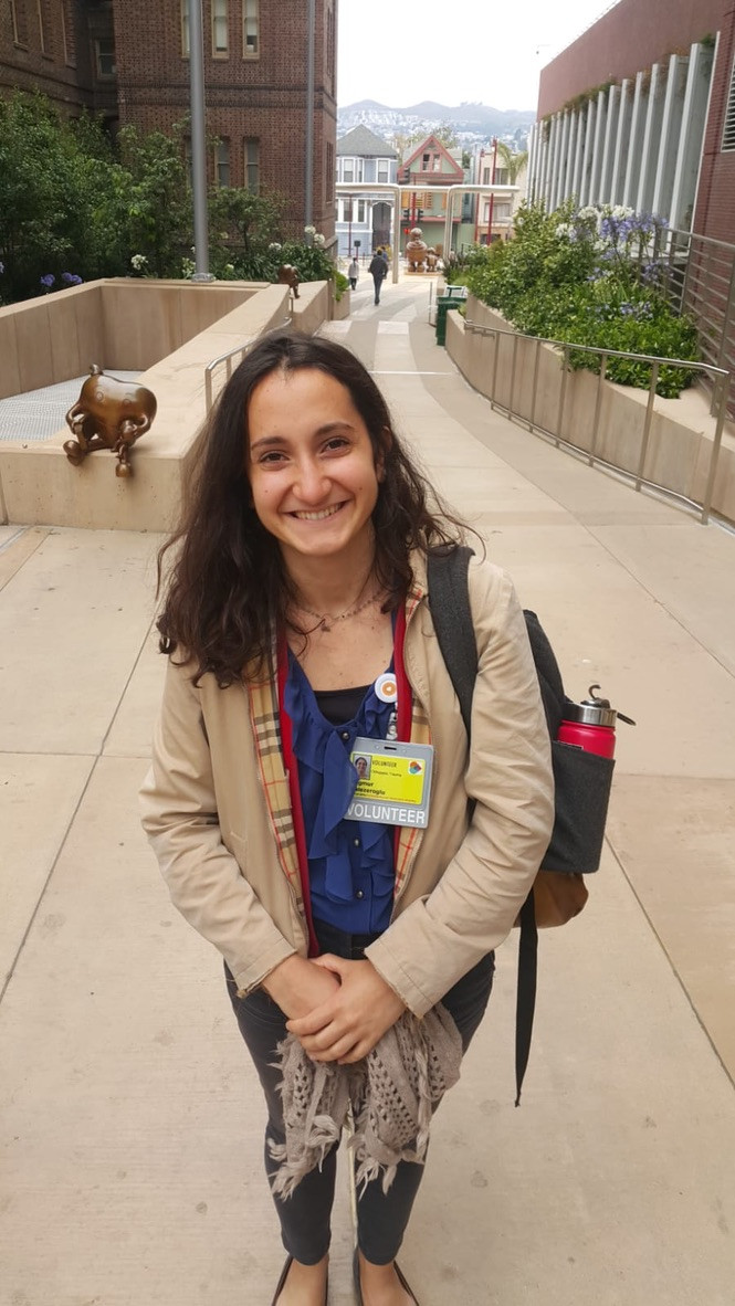 "Yagmur smiles as she poses in front of the hospital, with a backpack and beige colored jacket. She has fair skin and short dark brown hair. She wears a yellow badge that reads ""VOLUNTEER""."