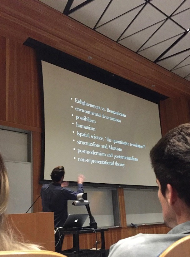 The professors points at the presentation as he explains the keywords listed on the slide projected to the screen in front of the lecture hall. The instructor has his back turned to the students, has short brown hair and wears a dark blue top.