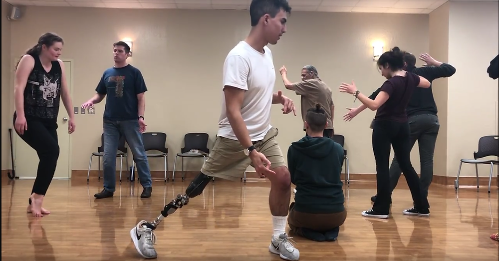 There are seven people in the photo, with a young man in the middle of the photo, extending his prosthetic right lower limb while he steps on his left foot. Everyone else is holds a different move with their arms, while one individual sits on the floor with their knees bent. The photo is taken in a dance studio with bright hardwood floor and a beige wall paint.