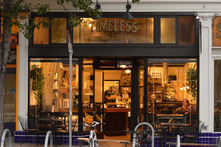 A photo of Timeless Coffee in Oakland. The coffee shop is photographed from the street, with wide glass windows and dark brown window muntins. Inside the coffeeshop there are chairs and seating and a counter. There is a tree on the left that has branches reaching towards the TIMELESS label on the center glass window seen on top of the photo.