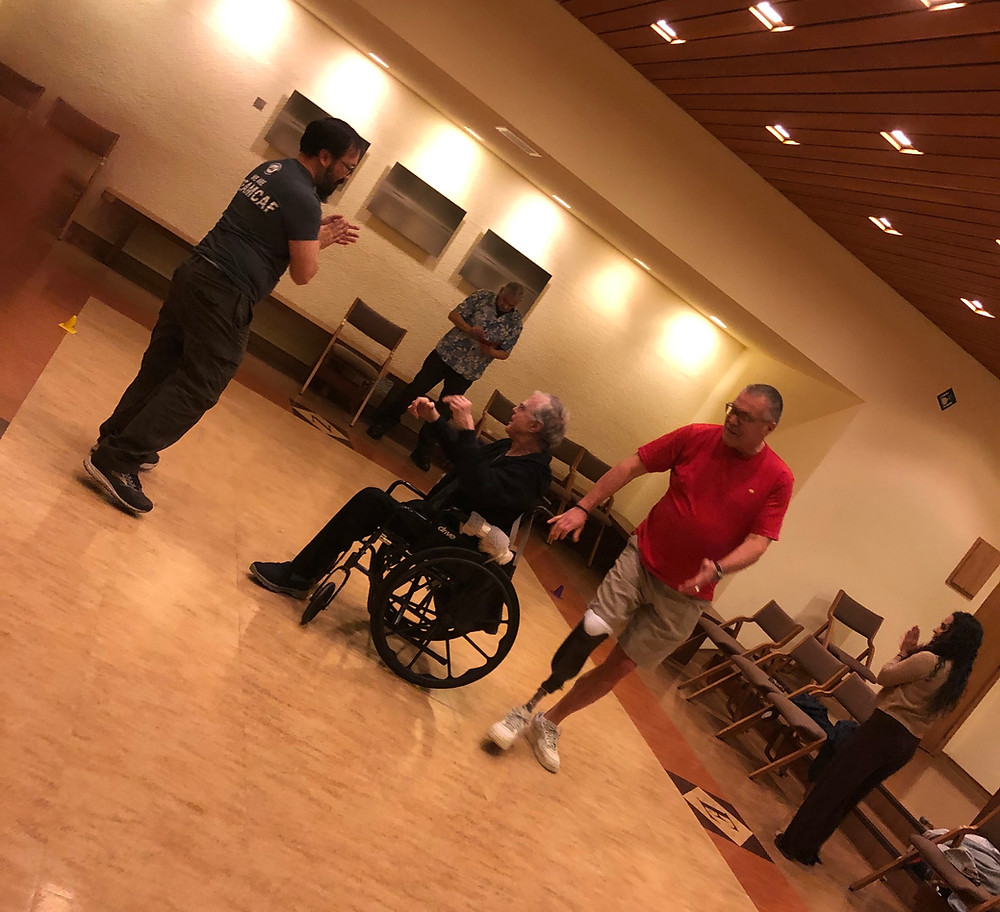 Three participants at amputee support group pictured together as they are dancing. One of the participants is in a wheelchair, and two other participants are standing. One of the participants on the right has their prosthetic for their right lower limb exposed.