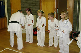 Junior students receiving tape on their belts for knowing their stances