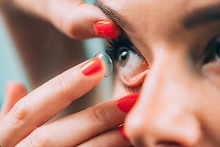 women putting in soft contact lens