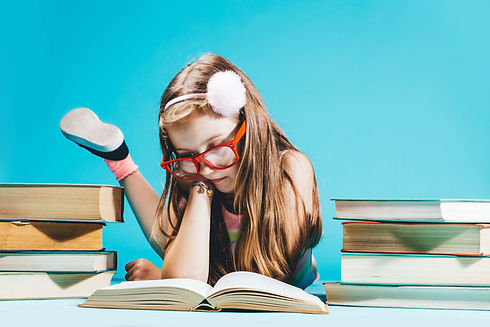 Young girl wearing glasses and reading a book