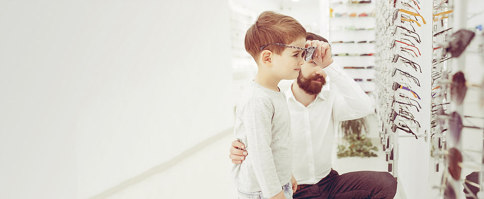 Young boy trying on glasses at Bennett & Rogers Opticians