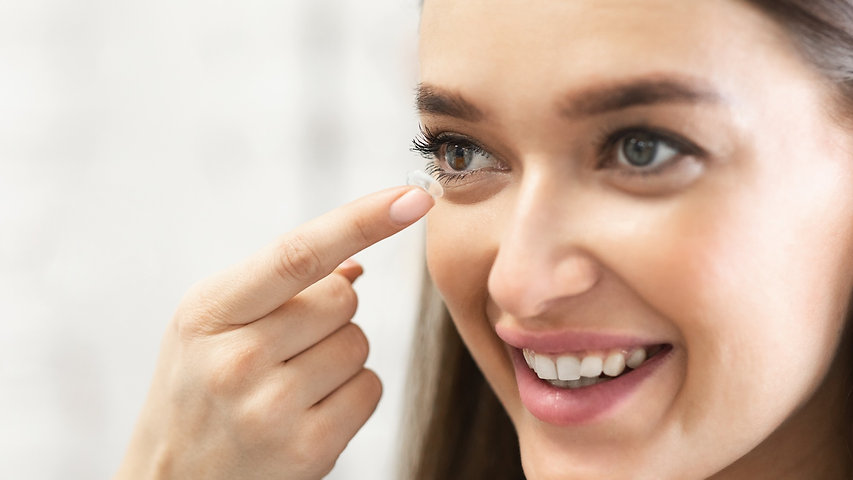 Young woman applying contact lens