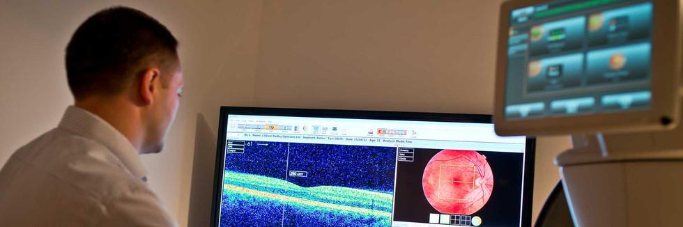 Optometrist checking eye test results at  J. Oliver Radley