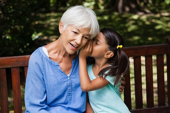 Girl whispering to Grandmother
