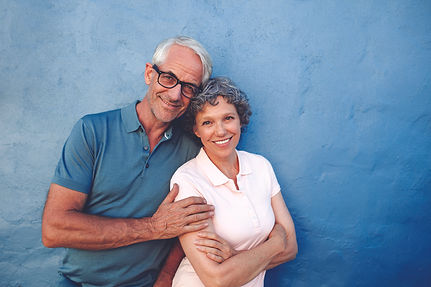 Smiling Happy Couple against a Blue Wall